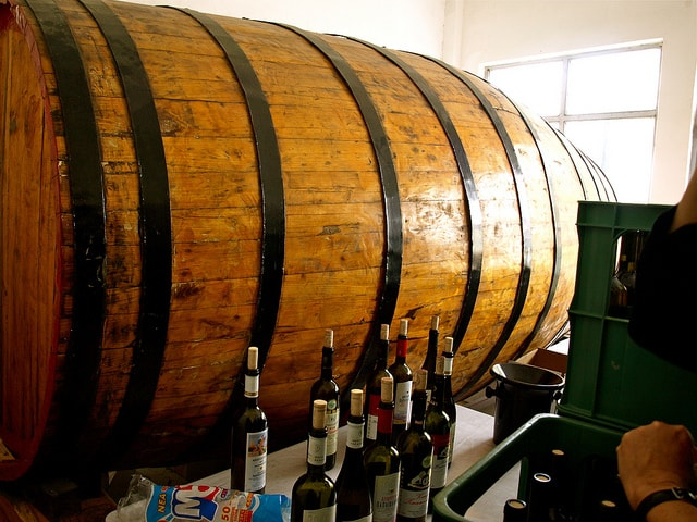 Image of ten bottles of wine in front of a big barrel in winery. Some of the best names in greek wine varietals.