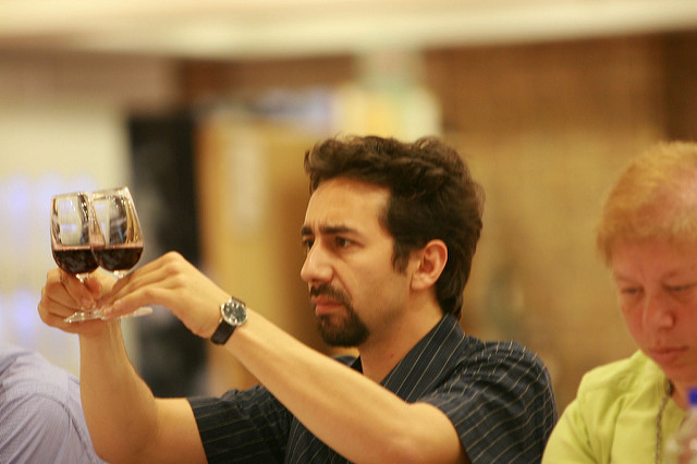 Photo of young man examining red wine while holding two glasses.