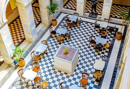 Have a coffee in the beautiful marble courtyard inside the Town Hall of Ermoupolis. One of the best things to do in Syros.