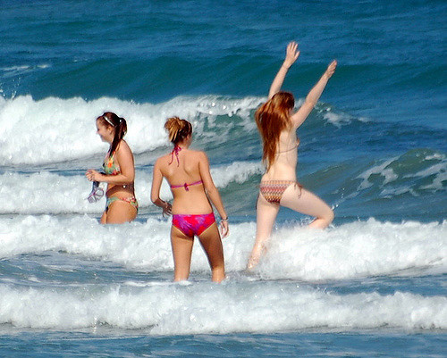 Three young girls playing in sea waves.