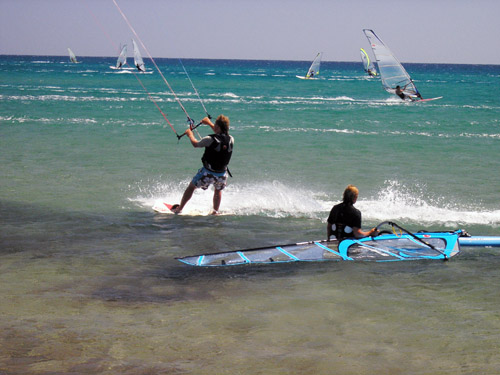 Image of two young people performing the activity of windsurfing during their holidays in Greece.