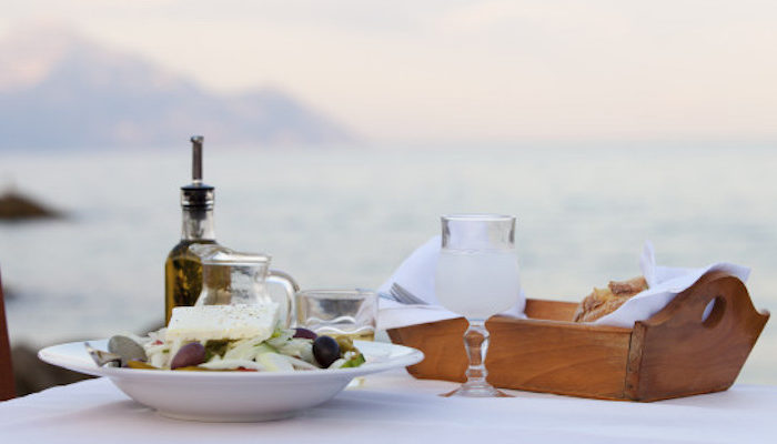 Enjoying a traditional Greek dinner by the sea.